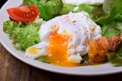 Poached egg with liquid yolk and green salad. On a white plate royalty free stock images