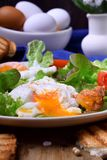 Poached egg with liquid yolk and green salad. On a white plate stock photos