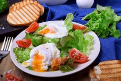 Poached egg with liquid yolk and green salad. On a white plate royalty free stock photos