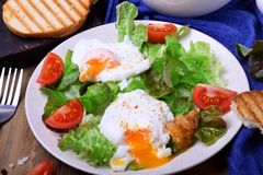 Poached egg with liquid yolk and green salad. On a white plate royalty free stock photo