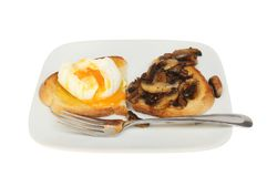 Poached egg and mushrooms. On toast with a fork on a plate isolated against white Stock Images