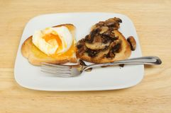 Poached egg and mushrooms on toast. Poached egg and fried mushrooms on toast on a wooden tabletop Royalty Free Stock Images