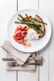 Poached egg, parma and asparagus. Breakfast with poached egg, parma and asparagus on white wooden background Stock Photo