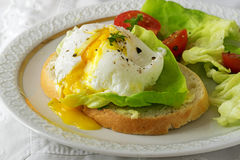 Poached egg with running yolk on baguette slice with salad and t Stock Photography