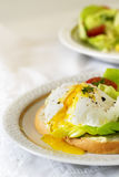 Poached egg with running yolk on baguette slice with salad and t Royalty Free Stock Images