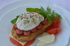 Poached egg, sausage, bread, feta chesse, tomato on pink napkin. Poached egg, sausage, bread, feta cheese, tomato on white plate on pink background Royalty Free Stock Photography