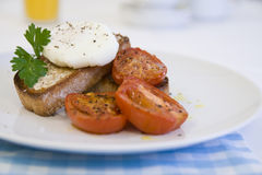 Poached egg on toast. Breakfast or Brunch of Poached egg on toast and tomatoes Royalty Free Stock Photography