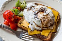 Poached Egg on Toast Bread with Cheddar Cheese, Balsamic Vinegar, Salad and Black Sesame or Cumin Seeds. Royalty Free Stock Photo