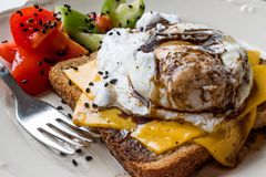 Poached Egg on Toast Bread with Cheddar Cheese, Balsamic Vinegar, Salad and Black Sesame or Cumin Seeds. Royalty Free Stock Images