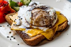 Poached Egg on Toast Bread with Cheddar Cheese, Balsamic Vinegar, Salad and Black Sesame or Cumin Seeds. Stock Photo