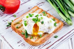 Poached egg on toast. On a wooden case background Stock Photo