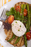 Poached egg on toasted bread with asparagus, tomatoes and greens Stock Photo