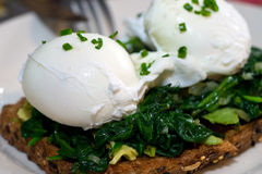 Poached egg on whole grain toast topped with avocado and spinach Royalty Free Stock Photography
