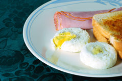 Poached Eggs with Ham. And Toast on a green placemat Royalty Free Stock Image