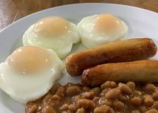 Three poached eggs, sausage, and baked beans for breakfast. royalty free stock photo
