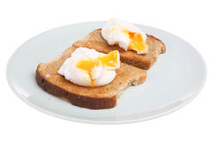 Poached Eggs on Toast. Two poached eggs on wholemeal buttered toast Stock Image