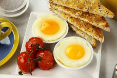 Poached Eggs And Tomatoes. Delicious poached eggs and grilled tomatoes with toast Royalty Free Stock Image