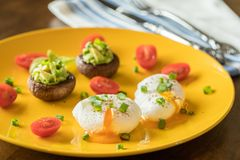Free Poached Eggs With Avocado Stuffed Mushrooms, Tomatoes, And Green Onions On A Cheery Yellow Plate Royalty Free Stock Photo - 139487035