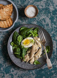 Poached mackerel, spinach and egg salad on a dark background, top view. Delicious healthy food