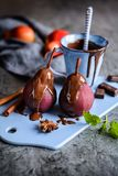 Poached pears in red wine and topped with chocolate sauce. Delicious spiced red wine poached pears topped with chocolate sauce Stock Photos