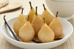 Poached pears in white wine. Whole poached  Gieser Wildeman pears in white wine with vanilla and cinnamon Stock Photography