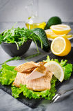 Poached salmon, arugula and lemon. Gray concrete background stock photos