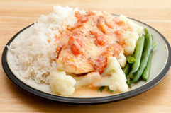 Poached tilapia fish fillets. A heart healthy meal of poached tilapia fish fillets with heirloom tomatoes and beans over white rice stock photo