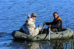 2 poachers на резиновой шлюпке улавливают рыб в сети Стоковые Фото