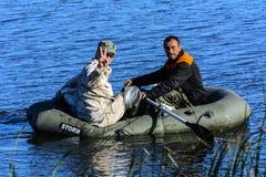 2 poachers на резиновой шлюпке улавливают рыб в сети Zhitomir Стоковые Изображения