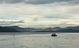 Poachers on motor boat collect catch in Avacha Bay. Poachers on a motor boat collect catch in Avacha Bay stock image
