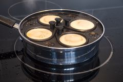 Poaching Four Eggs for Breakfast in an Egg-Poaching Pan 2 royalty free stock photography
