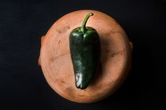 Poblano pepper. On rustic pot royalty free stock image