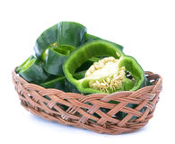 Poblano pepper. Sliced poblano pepper on bamboo basket on white background stock images