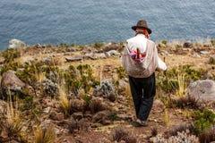 Pobre hombre que camina abajo de un acantilado, isla de Taquile, lago Titicaca, Perú Imagen de archivo libre de regalías
