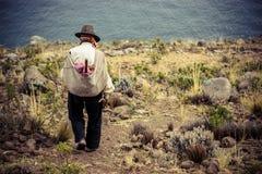 Pobre hombre que camina abajo de un acantilado, isla de Taquile, lago Titicaca, Perú Imagenes de archivo