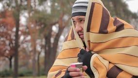 Pobre homem com a cara triste que esconde do frio na cobertura gasto, aquecendo-se com chá quente filme