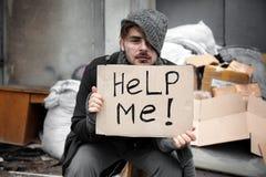 Pobre homem com PARA AJUDAR-ME a assinar na descarga fotos de stock royalty free