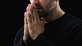 Pobre homem doente que reza ao deus contra o fundo escuro, cristandade, opinião filme