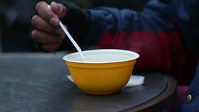 Pobre homem esfomeado que come avidamente a sopa quente da bacia plástica no abrigo desabrigado filme