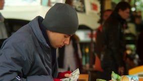 Pobre homem no restaurante de fastfood que conta o dinheiro roubado no papel video estoque