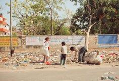 Pobreza en la acción, familia de niños pobres y padre que busca desperdicios plásticos en montón de basura para ganar el penique Fotos de archivo