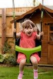 Pobudliwa młoda dziewczyna śmia się podczas gdy bawić się na huśtawkach obrazy stock