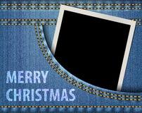 圣诞快乐问候和空白的照片框架在蓝色牛仔裤poc 库存照片