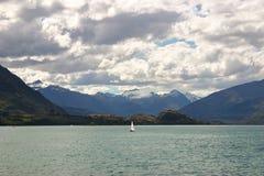 Poca barca a vela in mezzo al lago Tekapo, Nuova Zelanda Fotografia Stock