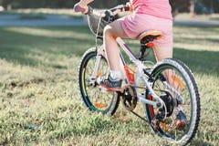 Poca bicicleta morena del montar a caballo de la muchacha en el parque en la puesta del sol Imagen de archivo
