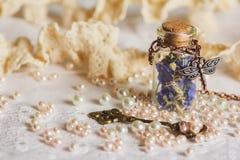 Poca botella por completo con las flores secadas coloridas fotos de archivo