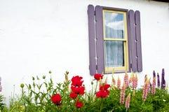 Poca cabaña blanca del estuco enmarcada con las flores Imagenes de archivo