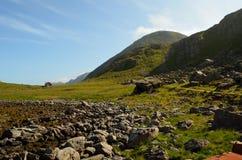 Poca cabina sola rossa accanto alla montagna ed alla spiaggia alte Fotografia Stock