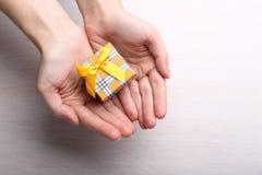Poca caja de regalo en manos femeninas en fondo de madera Fotos de archivo