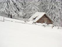 Poca capanna coperta in neve in montagne fotografia stock libera da diritti